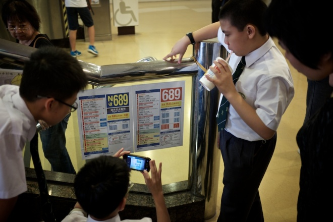School children laugh and joke around a fake bus schedule that mocks CY Leung.