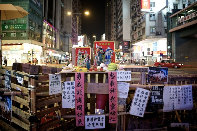 A clever thinking protester created this shrine for the barricade in Mong Kok. Guan Gong represents justice. He is inside every police station. Some people wonder how the police will now take down this barricade as doing so will curse the station and the families of police officers. From Left to right :  White paper - Guan gong don't protect police who gang up with thugs. Pink paper -  Fearless to protect the country and its people.  Middle white paper - Blasphemy will be punished by gods.  Pink paper - God will protect those who are kind and loyal.